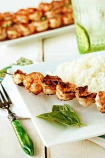 Marinated grilled shrimp on a skewer next to white rice on a plate