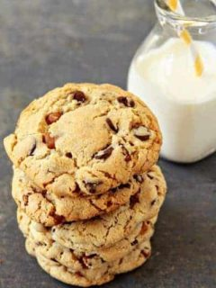 A stack of turtle cookies in front of a glass of milk of a stone surface