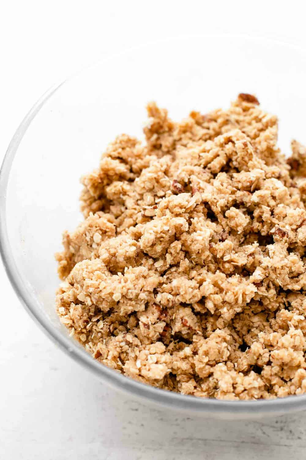 Crumble topping for apple pie bars in a glass mixing bowl