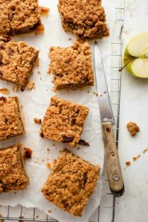 Baked apple pie bars with crumble topping, sliced and on parchment paper