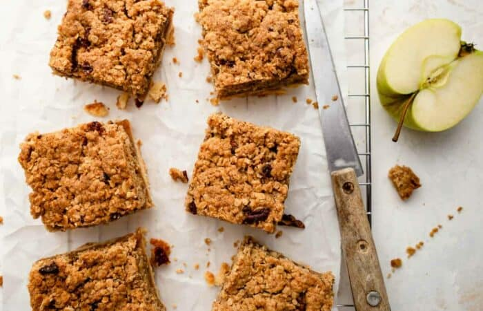 Sliced apple pie bars on parchment paper next to an apple and knife
