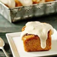 Pumpkin cinnamon roll on a plate in front of a pan of pumpkin cinnamon rolls