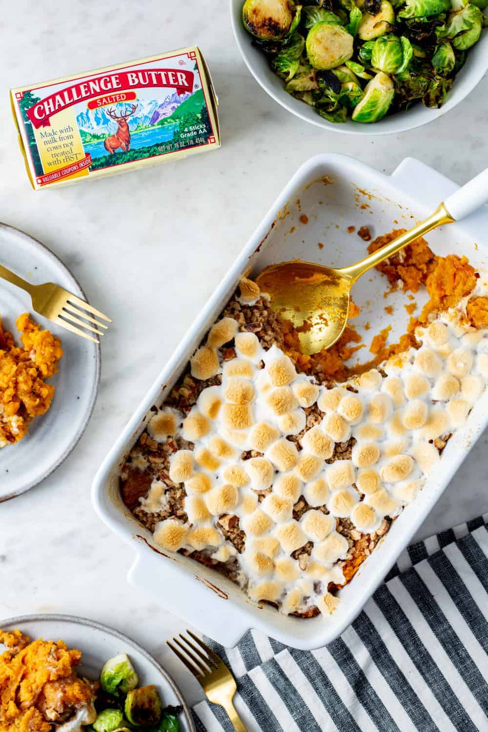 Spoon dishing out sweet potato casserole with streusel topping and sweet potatoes
