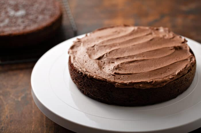Single layer of chocolate cake topped with chocolate frosting on a white cake stand on a wooden background