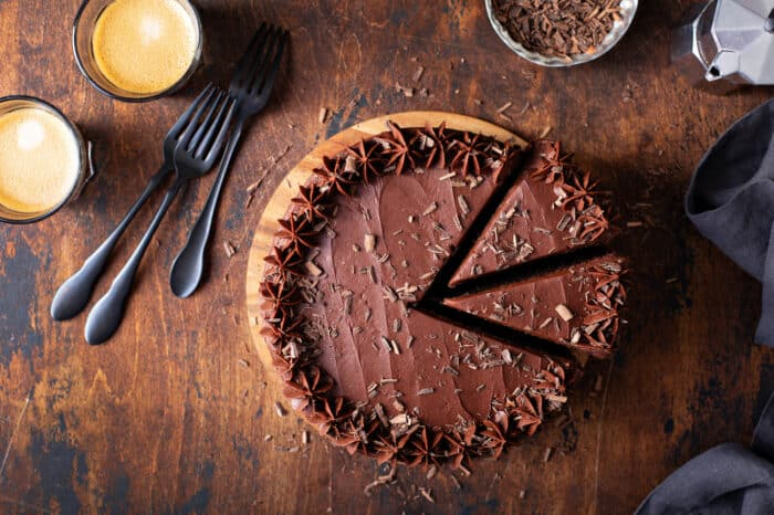 Overhead view of chocolate-frosted cake with 2 slices cut on a wooden cutting board