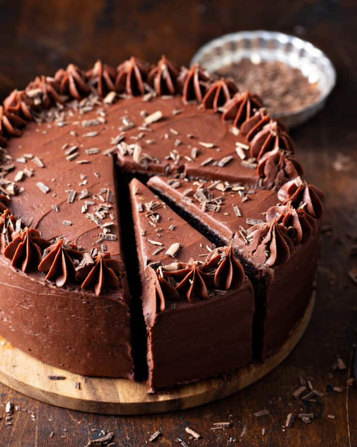 Chocolate cake with chocolate frosting on a wooden cake stand with two slices cut