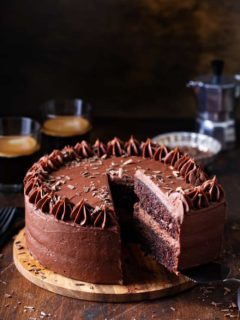 Slice being removed from a double layer chocolate cake with chocolate frosting, with coffee in the background