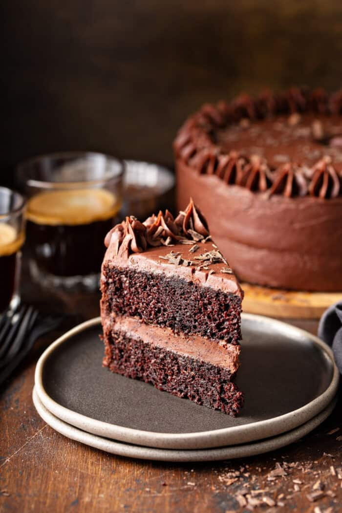 Slice of chocolate cake with chocolate frosting on a gray plate with coffee and chocolate cake in the background