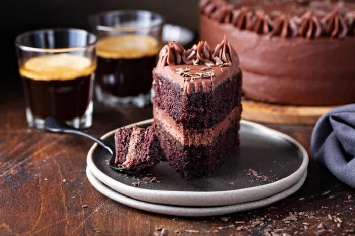 Slice of double-layer chocolate cake with chocolate frosting on a gray plate with a fork taking a bite out of the cake
