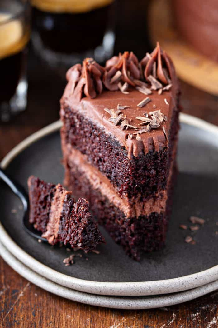 Fork taking a bite out of a slice of chocolate-frosted chocolate cake on a gray plate