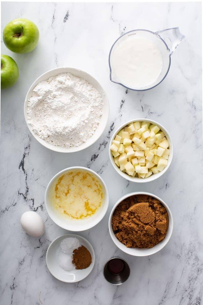 Visão aérea dos ingredientes para muffins de maçã e canela dispostos em um balcão de mármore