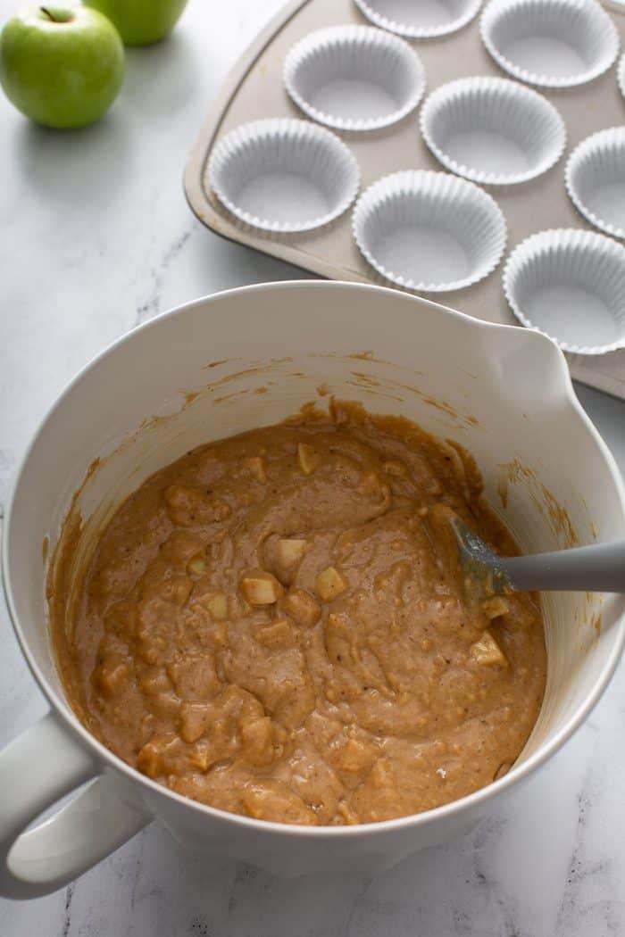 Massa de muffin de maçã com canela e uma espátula cinza em uma tigela branca com uma forma de muffin forrada com forros de papel no fundo