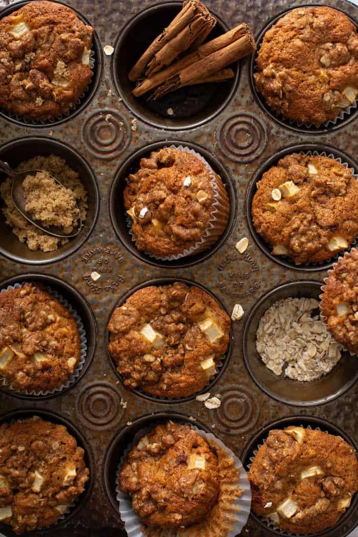Muffins de maçã e canela dispostos em uma lata de bolinhos manchada