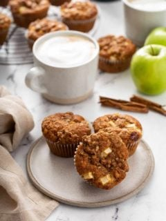 Three apple cinnamon muffins on a cream plate with lattes and more muffins on a cooling rack in the background