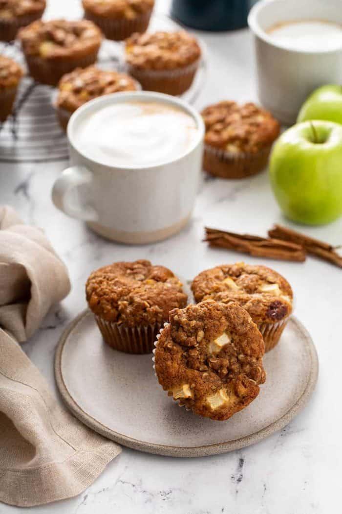 Três muffins de maçã e canela em um prato de creme com café com leite e mais muffins em uma grade de refrigeração ao fundo