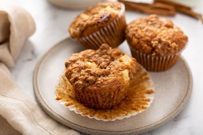 Três muffins de maçã e canela em um prato de creme