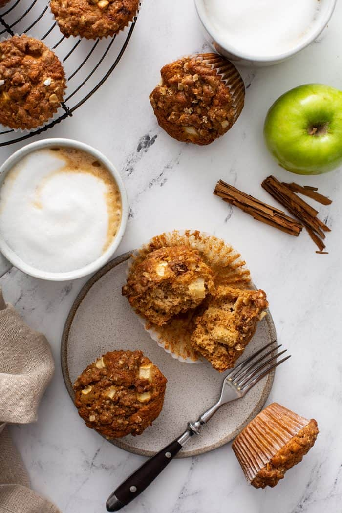 Overhead view of two apple cinnamon muffins next to a fork on a gray plate, surrounded by lattes, apples and more muffins