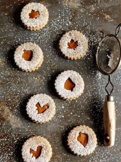 Overhead photo of Linzer cookies with different fall cutouts sprinkled with powdered sugar