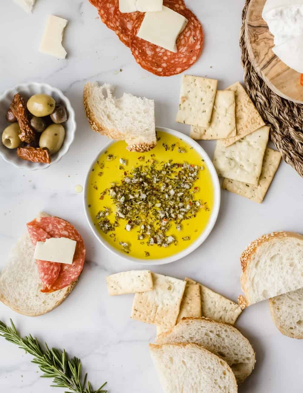 Shallow bowl of olive oil herb dip on a white platter with bread, olives and cured meats