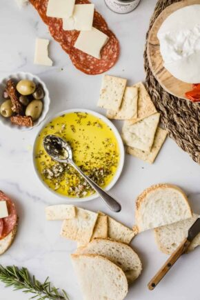 Spoon in a bowl of olive oil herb dip surrounded by bread, olives and charcuterie