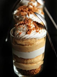 Pumpkin cheesecake trifles lined up with spoons leaning on the side
