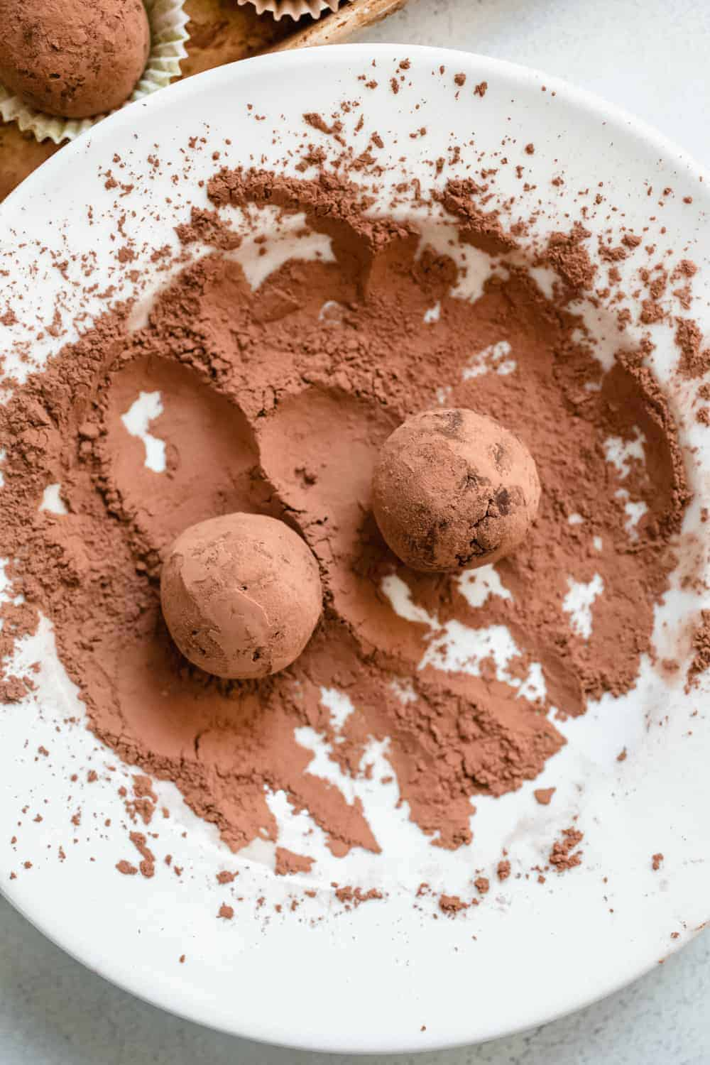 Two rum balls being rolled in a shallow bowl of cocoa powder
