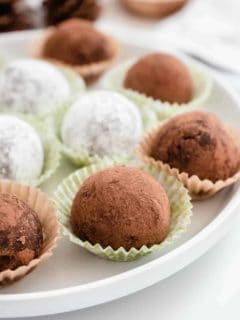 Rum balls coated in both cocoa powder and powdered sugar arranged on a plate