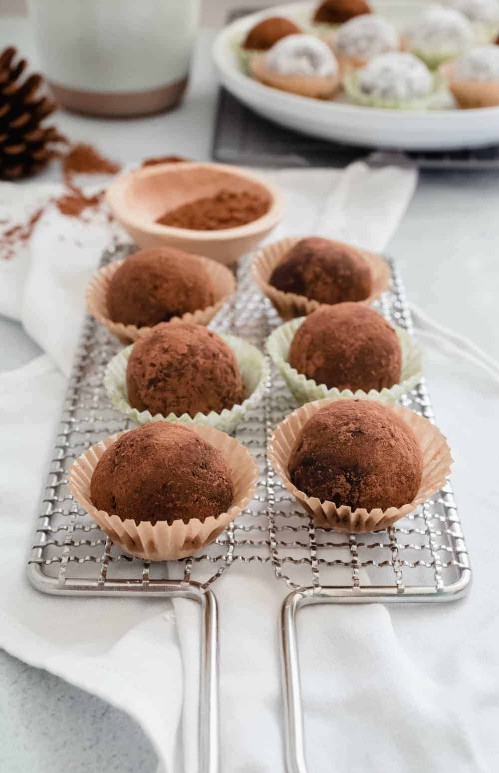 Side view of rum balls rolled in cocoa powder and arranged in mini baking cups