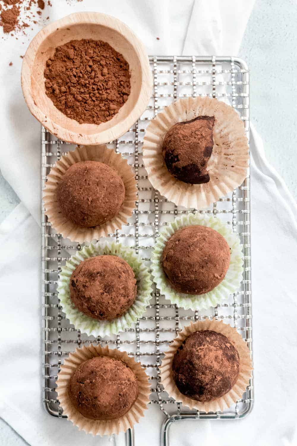 Rum balls arranged in mini baking cups on a baking rack, with a bite taken out of one
