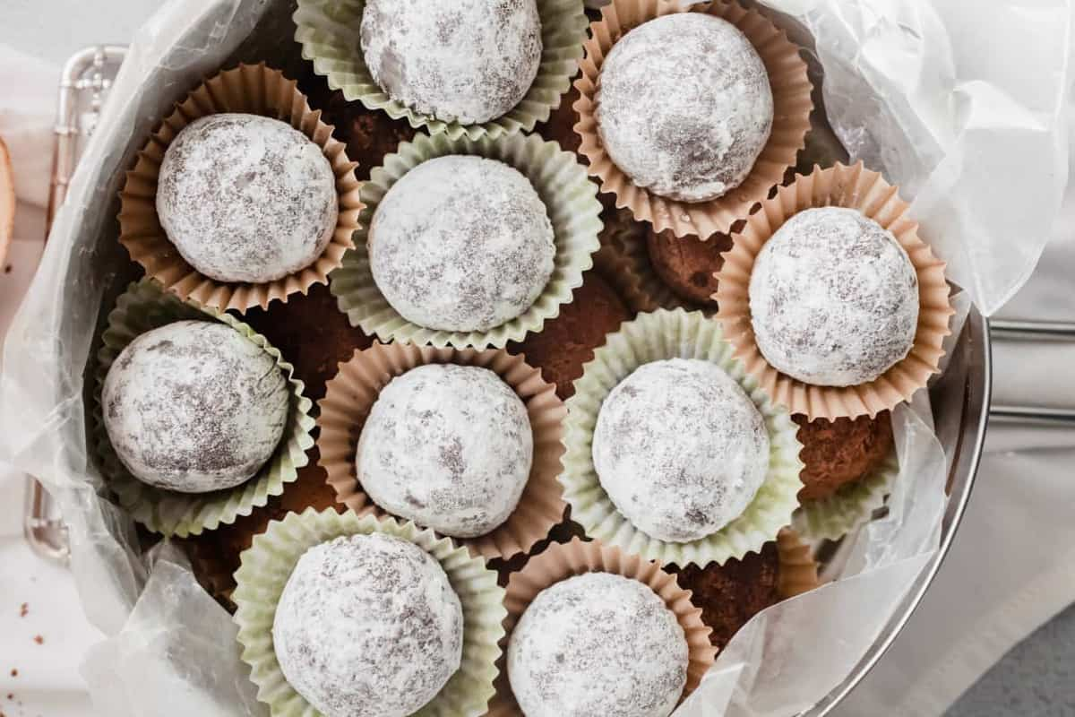 Close up of rum balls rolled in powdered sugar arranged in baking cups