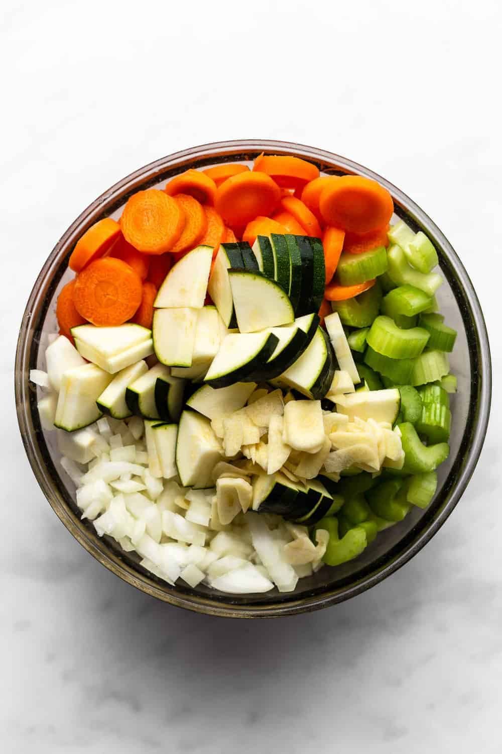 Overhead shot of diced onions, carrots, celery and zucchini in a bowl on a white surface