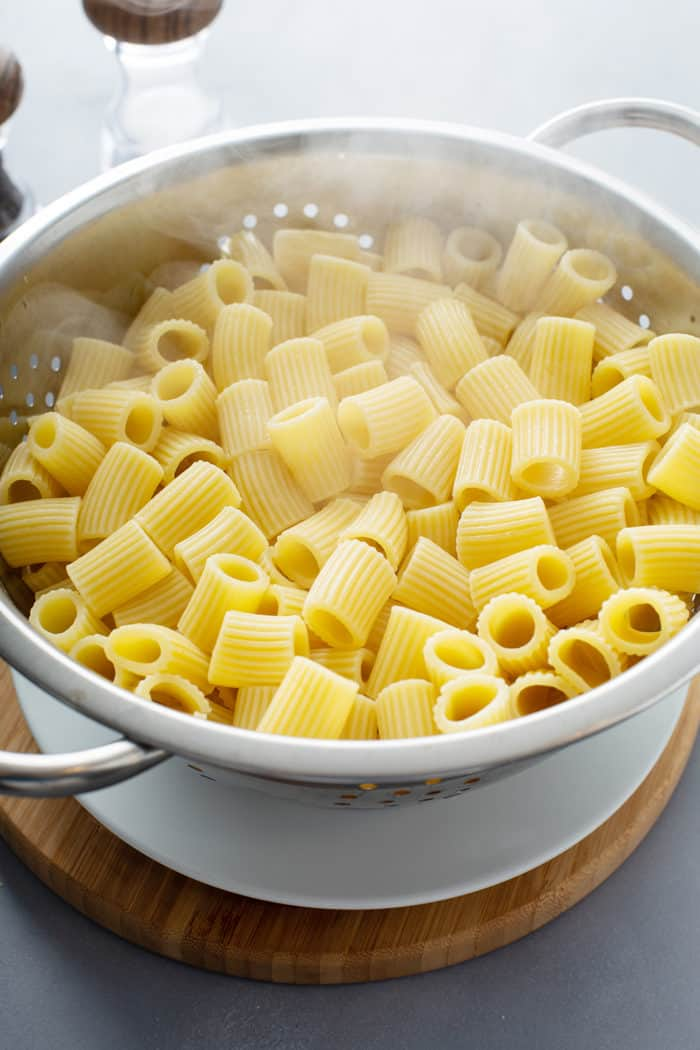 Freshly cooked rigatoni pasta in a colander