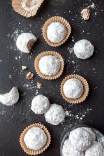 Snowball cookies arranged on a slate surface.
