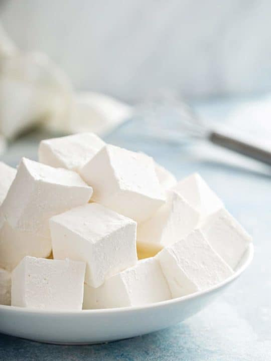 Large white bowl filled with homemade marshmallows on a blue countertop