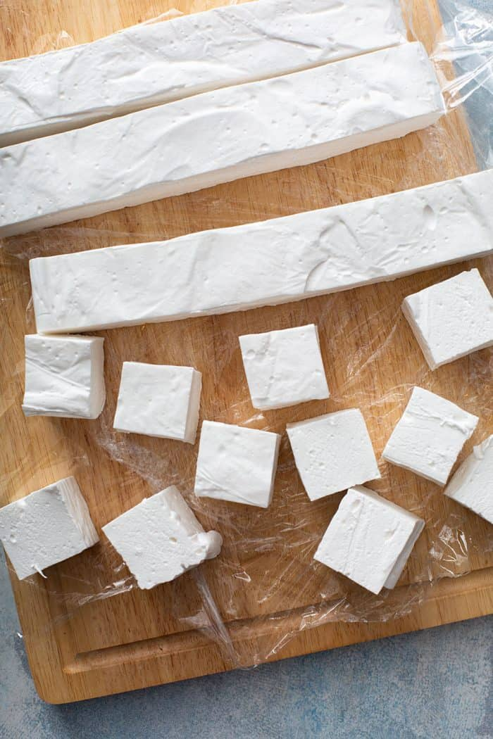 Homemade marshmallows being sliced on a wooden cutting board