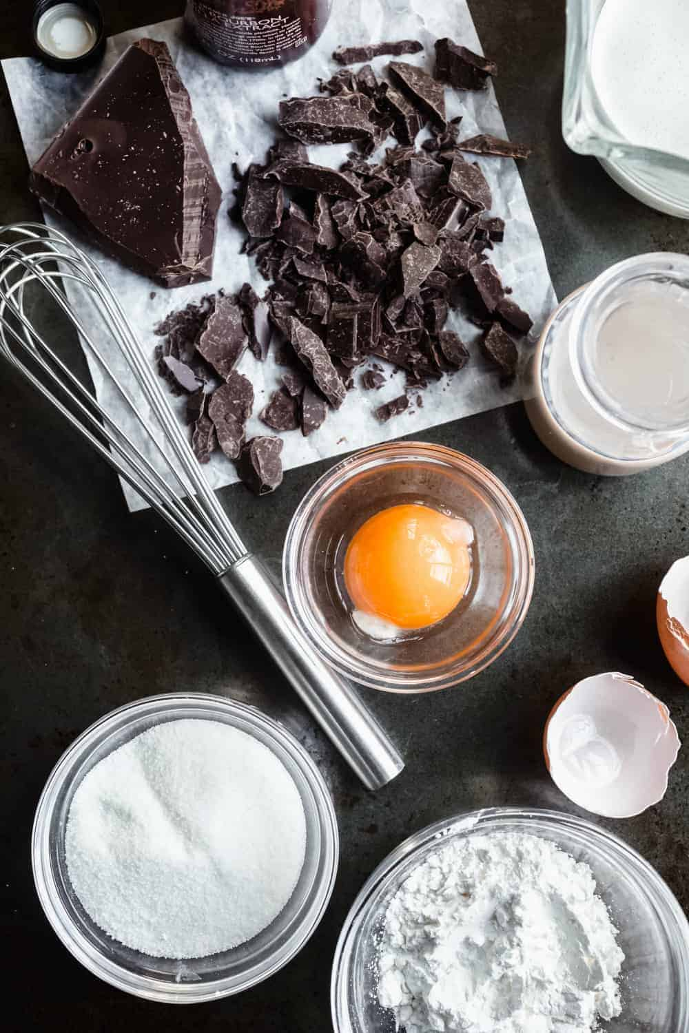 Ingredients for homemade chocolate pudding with Baileys arranged on a black countertop