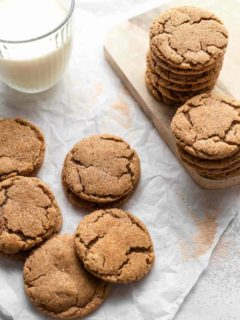 Chai sugar cookies stacked next to a glass of milk
