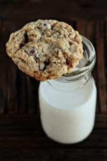 An oatmeal raisinet cookie on top of a glass of milk