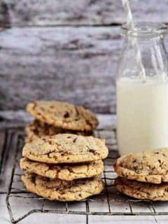 Stacks of toffee almond cookies on a cooling rack with a glass of milk