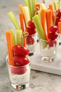 Small shot glasses full of dill dip and assorted veggies