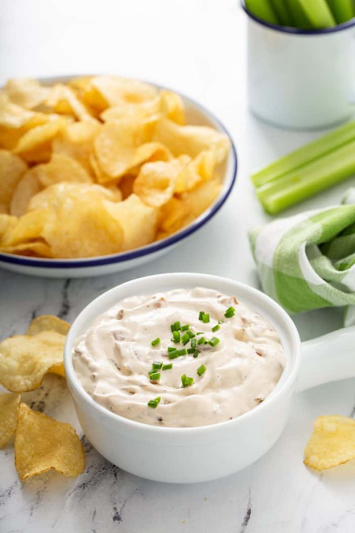 Bowl of french onion dip with potato chips and celery sticks in the background