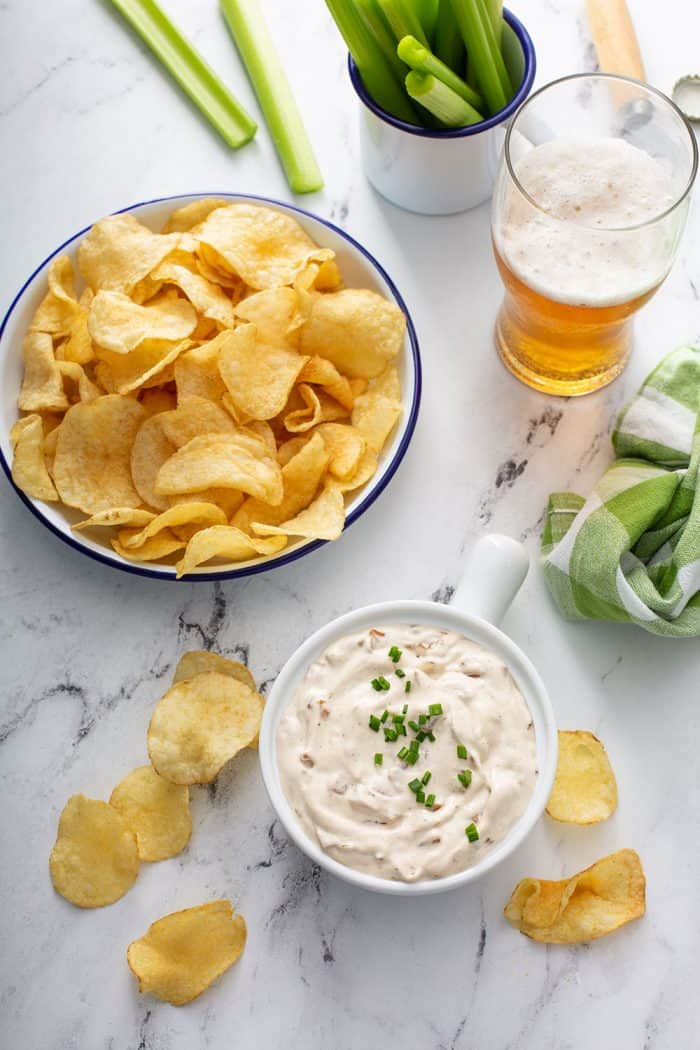 Overhead view of a bowl of french onion dip on a counter next to a bowl of potato chips and a glass of beer