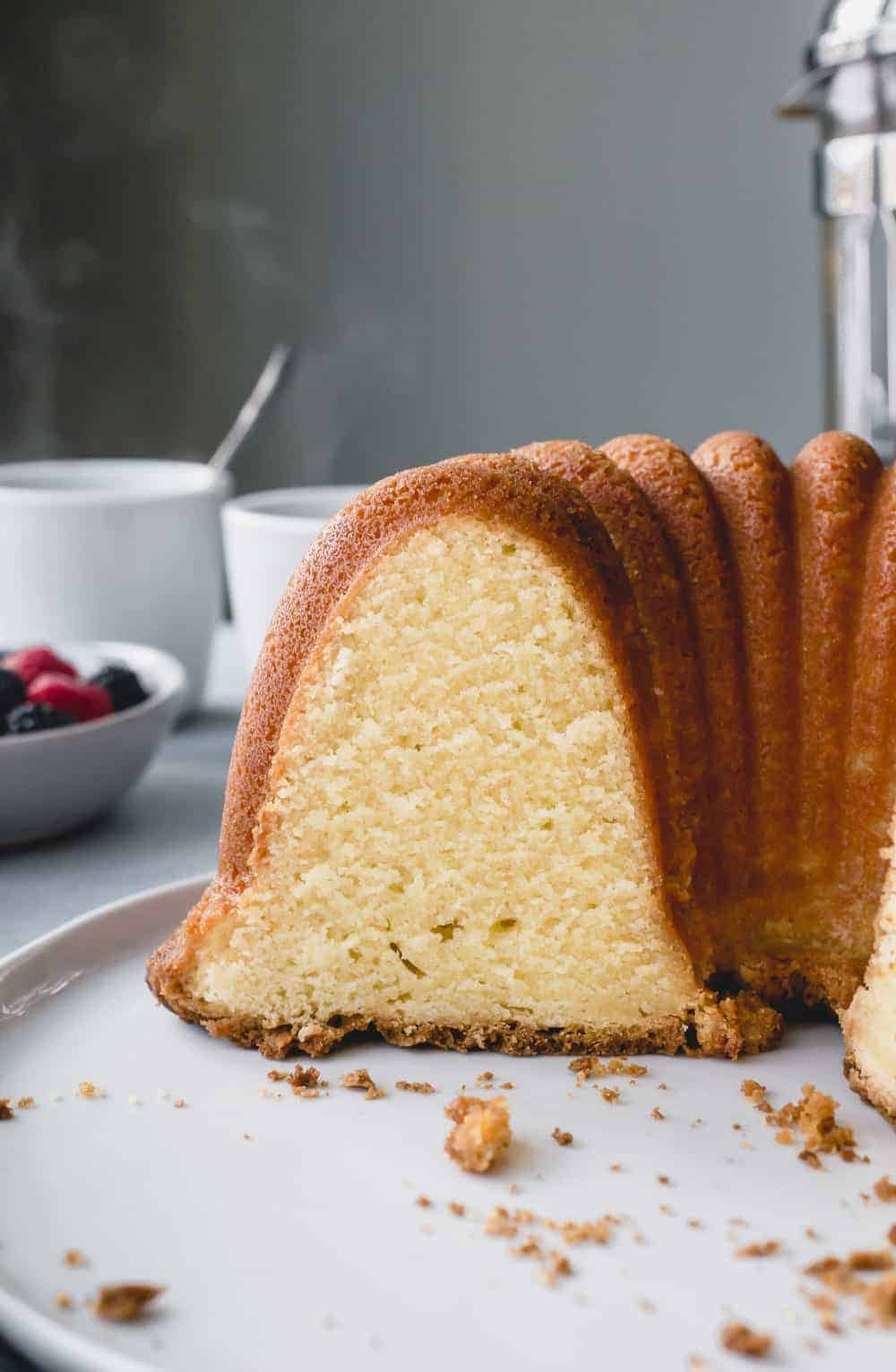 Sliced 7up pound cake on a cake plate in front of a bowl of berries