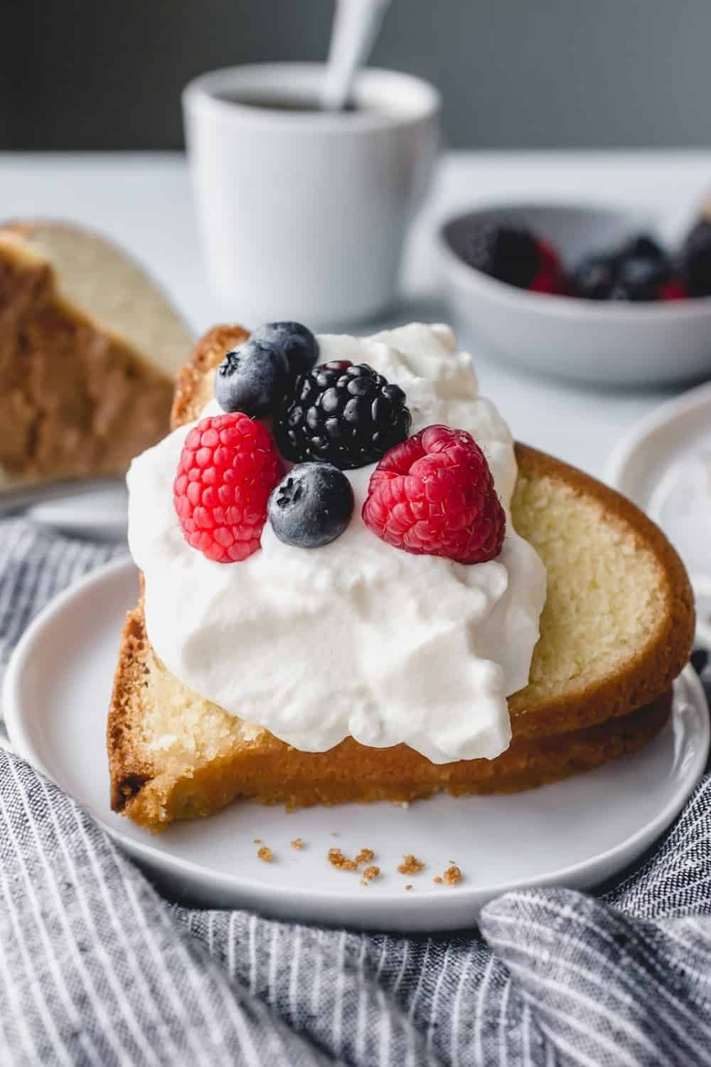 Close up of a slice of 7up pound cake topped with whipped cream and fresh berries