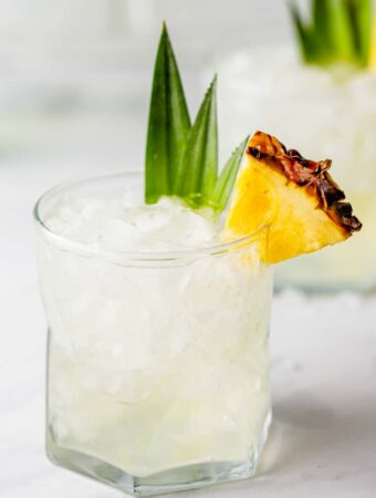 Pineapple vodka in a rocks glass, garnished with a slice of pineapple