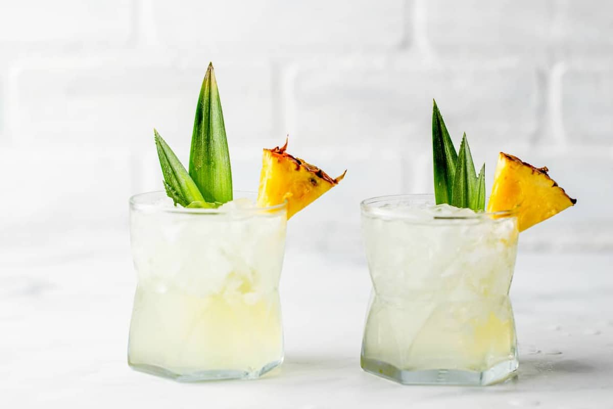 Two glasses of Stoli Doli on the rocks, garnished with pineapple