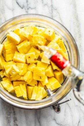 Vodka being poured over diced pineapple in a glass container