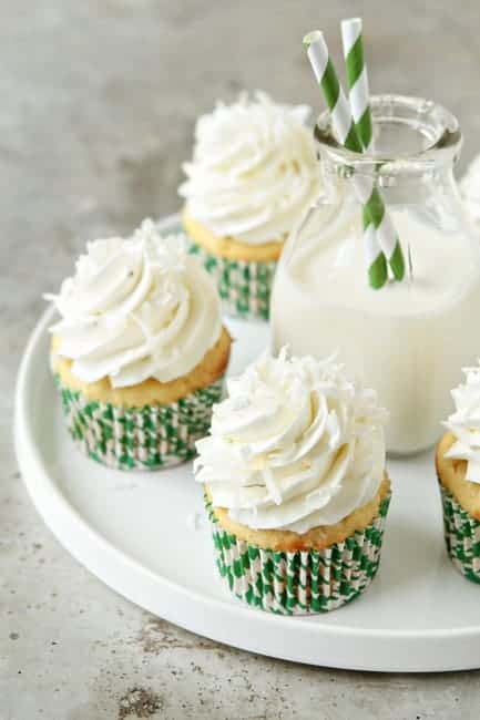 Coconut cupcakes on a round white plate with a glass of milk in the center