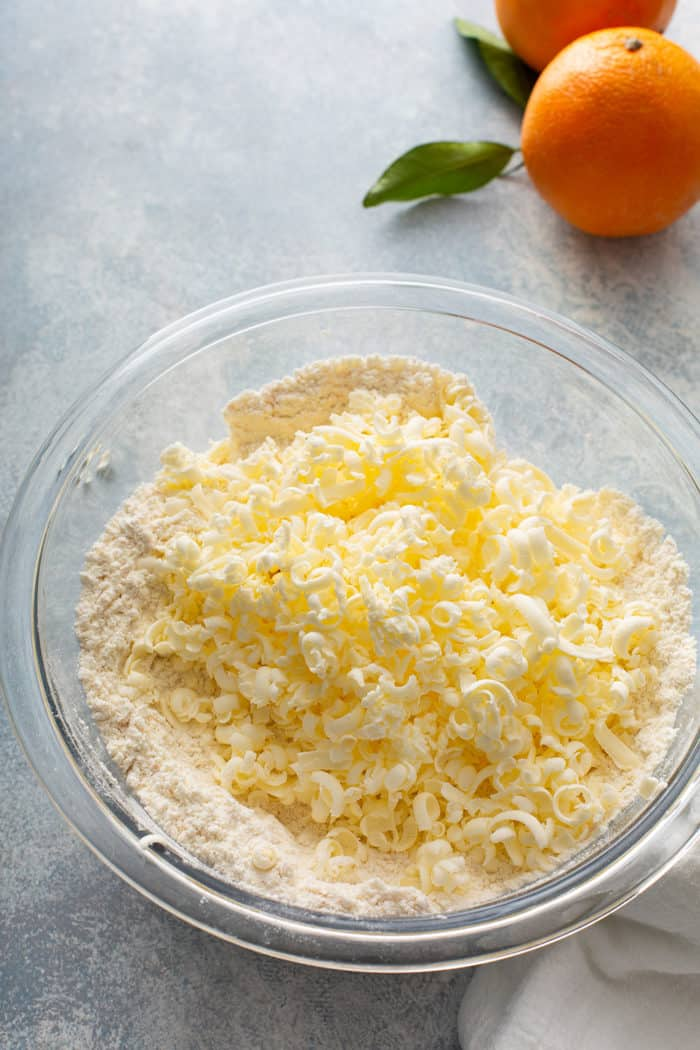 Grated butter added to dry ingredients for scones in a glass mixing bowl