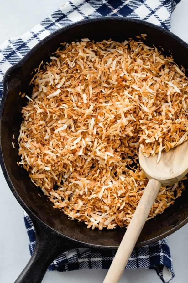 Toasted coconut in a cast iron skillet with a wooden spoon